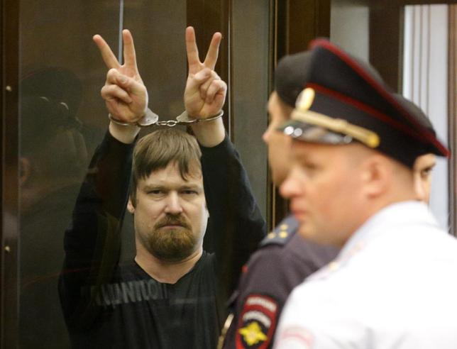 Leonid Razvozzhayev, co-defendant of opposition leader Sergei Udaltsov, gestures from the defendants cage during a court hearing in Moscow  July 24, 2014. REUTERS/Maxim Shemetov