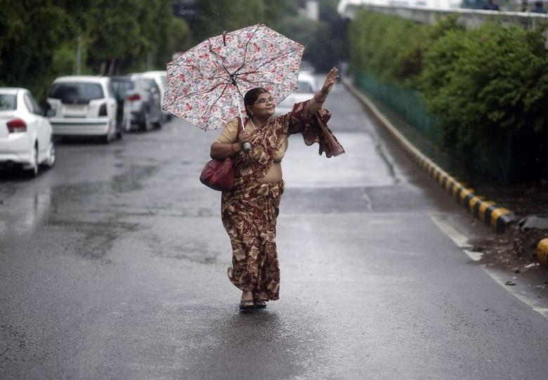 A woman signals for a bus to stop as she walks under an umbrella during rainfall in New Delhi July 17, 2014. REUTERS/Anindito Mukherjee/Files