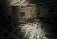 Банкноты российского рубля и доллара США в Москве 17 февраля 2014 года. Рубль показывает отрицательную динамику на торгах четверга из-за рисков объявления Евросоюзом новых санкций против России, часть из которых может носить экономический характер. REUTERS/Maxim Shemetov