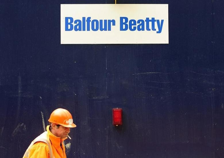 A worker strolls past a Balfour Beatty sign at a construction site in central London April 17, 2008. REUTERS/Dylan Martinez