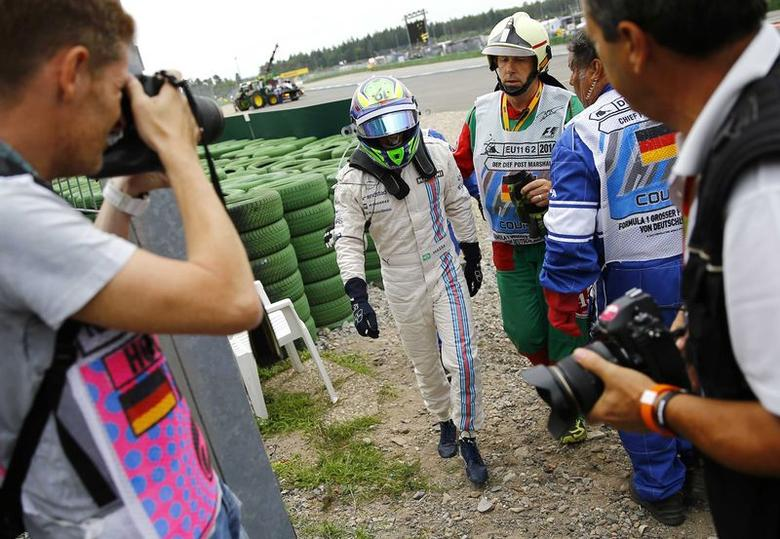 Williams Formula One driver Felipe Massa of Brazil walks off the track after crashing with his car in the first corner after the start of the German F1 Grand Prix at the Hockenheim racing circuit, July 20, 2014.  REUTERS/Kai Pfaffenbach