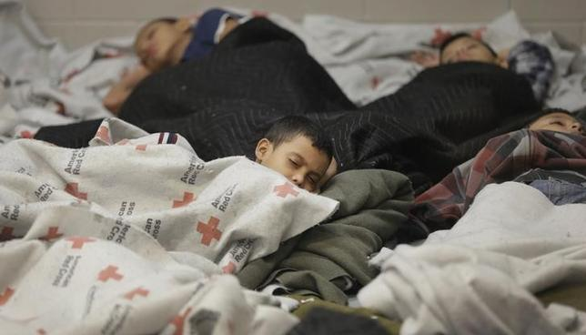 Detainees sleep in a holding cell at a U.S. Customs and Border Protection processing facility, in Brownsville, Texas June 18, 2014. REUTERS/Eric Gay/Pool