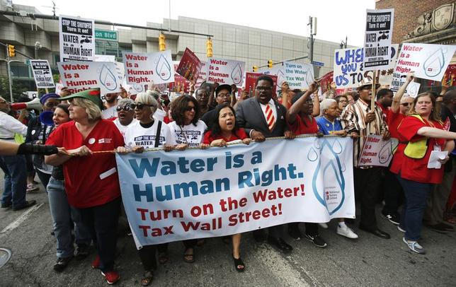 People hold a banner against the mass water shut-offs to Detroit citizens behind in their payments, during a protest in downtown Detroit, Michigan July 18, 2014. REUTERS/Rebecca Cook