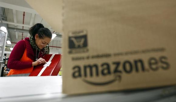 A worker packs a box at Amazon's logistics centre in Graben near Augsburg December 16, 2013. REUTERS/Michaela Rehle/Files