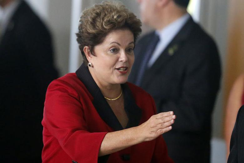 Brazil's President Dilma Rousseff gestures as she arrives to the official photo session for the 6th BRICS summit and the Union of South American Nations (UNASUR), in Brasilia July 16, 2014.  REUTERS/Sergio Moraes