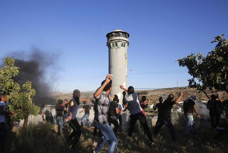 Palestinians throw stones at members of the Israeli army during the funeral of three Palestinians, who medics said were killed during clashes with Israeli troops, in Beit Ommar town north of the West Bank city of Hebron July 25, 2014.  REUTERS/ Mussa Qawasma