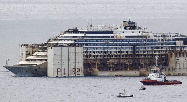 Tug boats tow the Costa Concordia ship as they arrive outside Genoa's port, in northern Italy, where the ship will be broken up for scrap, July 27, 2014.    REUTERS/ Stefano Rellandini