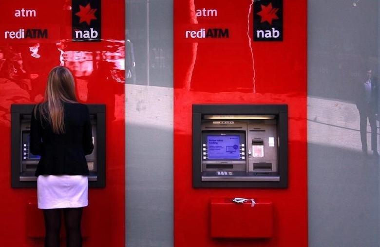 Man is reflected in a glass panel next to a woman using a National Australia Bank automated teller machine (ATM) in central Sydney May 9, 2013. REUTERS/David Gray