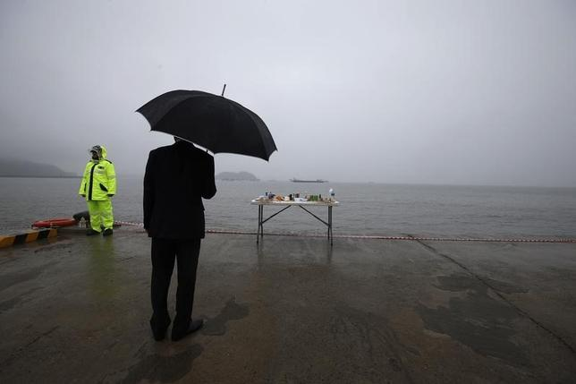 A man stands in front of an altar dedicated to the missing and dead passengers on board the capsized Sewol ferry, at a port in Jindo, April 28, 2014.  REUTERS/Kim Kyung-Hoon