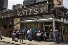 People stand in line at Katz's Delicatessen, the famous deli founded in 1888, in New York's lower East Side in this file photo taken June 13, 2014.   REUTERS/Brendan McDermid/Files
