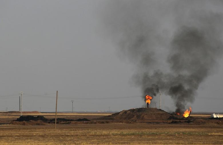 Smoke rises from an oil field in Al-Rmelan, Qamshli province November 11, 2013.  REUTERS/Stringer