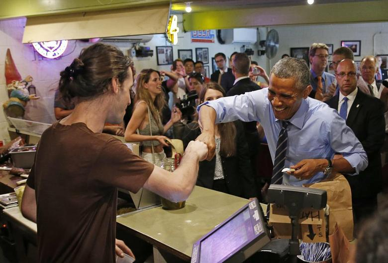 U.S. President Barack Obama fist bumps the cashier after paying for his order at Franklin Barbecue in Austin, Texas  July 10, 2014.   REUTERS/Kevin Lamarque
