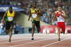 Kemar Bailey-Cole (C) of Jamaica finishes first place ahead of Adam Gemili (R) of England, and Jason Livermore of Jamaica during the men's 100m final at the 2014 Commonwealth Games in Glasgow, Scotland, July 28, 2014.         REUTERS/Andrew Winning