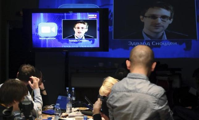 Journalists listen to a speech and a question posed by former U.S. spy agency NSA contractor Edward Snowden, at a media centre during Russian President Vladimir Putin's live broadcast nationwide phone-in, in Moscow April 17, 2014. REUTERS/Sergei Karpukhin/Files