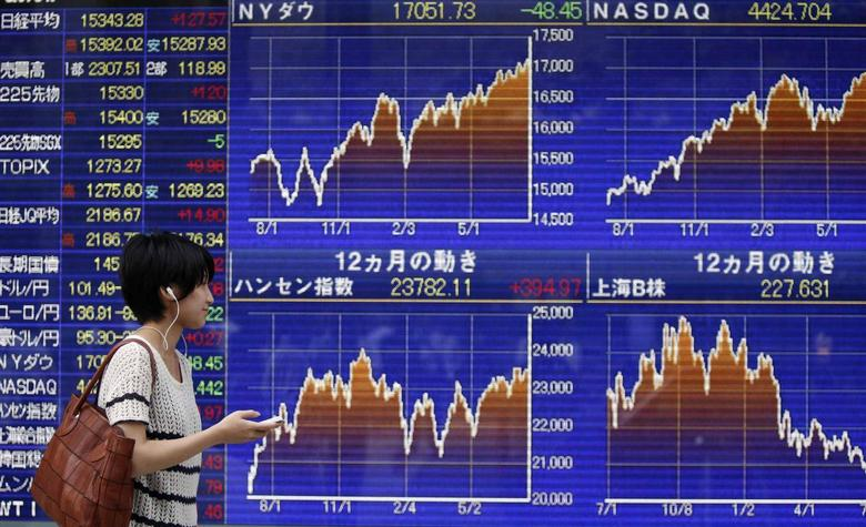A pedestrian holding her mobile phone looks at an electronic board showing graphs of various countries' stock market indices outside a brokerage in Tokyo July 22, 2014. REUTERS/Yuya Shino