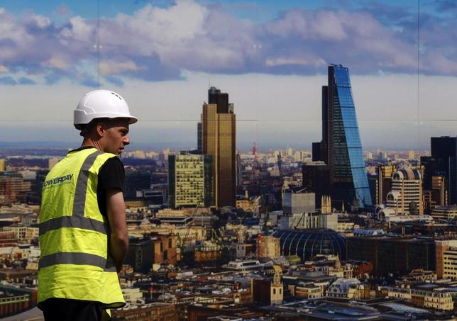 A worker walks past a picture of the London skyline outside the sales office of a property development in central London July 2, 2014.  REUTERS/Luke MacGregor