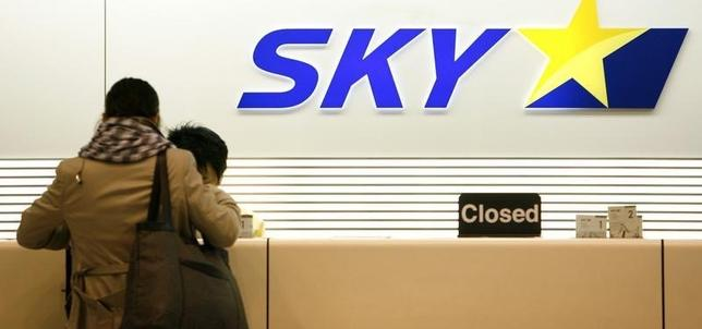 A woman checks in at a Skymark Airlines desk at Haneda airport in Tokyo January 17, 2009.   REUTERS/Stringer