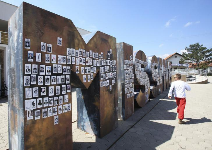 A Serbian boy walks near the ''Missing'' monument covered with pictures of missing Serbs, in Gracanica near the capital Pristina April 22, 2014.REUTERS/Hazir Reka