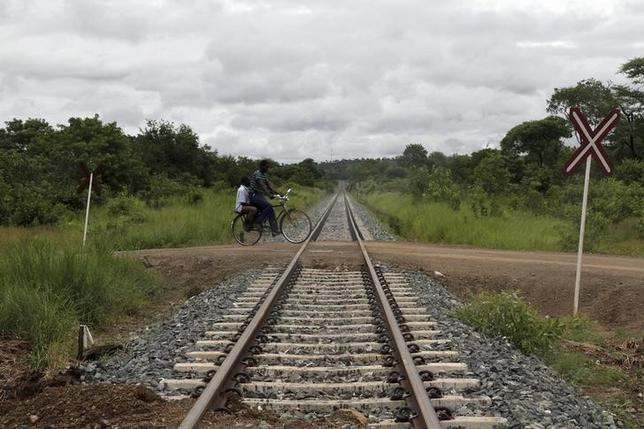 A man rides a bike over a railway line in Moatize in Tete province February 13, 2013 . REUTERS/Agnieszka Flak/Files