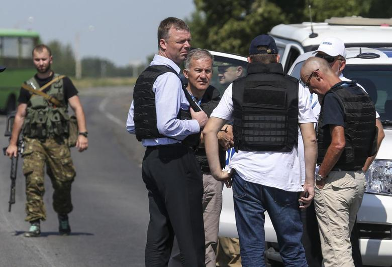 Alexander Hug (front C), deputy head for the Organisation for Security and Cooperation in Europe's (OSCE) monitoring mission in Ukraine, stands with members of his team on the way to the site in eastern Ukraine where the downed Malaysian airliner MH17 crashed, outside Donetsk, July 30, 2014. REUTERS/Sergei Karpukhin