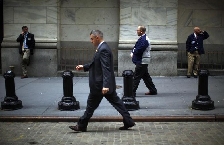 People walk and talk on cell phones along Broad Street in front of the New York Stock Exchange, March 27, 2009.  REUTERS/Eric Thayer