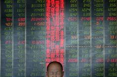 Инвестор в брокерской конторе в Тайюане, провинция Шаньси, 9 мая 2013 года. Азиатские фондовые рынки завершили торги четверга разнонаправленно на фоне фиксации прибыли в Японии и Южной Корее и роста акций продавцов недвижимости и горнорудных компаний в Шанхае и Гонконге. REUTERS/Jon Woo