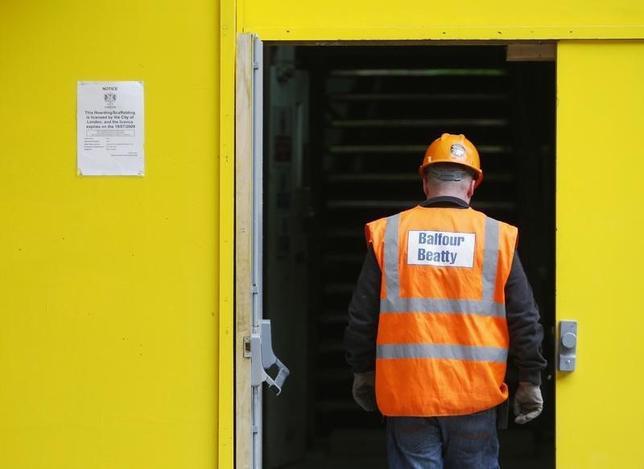 A Balfour Beatty construction worker walks onto a site in London August 10, 2009.   REUTERS/Luke MacGregor