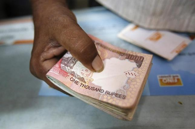 A customer hands a bundle of Indian Rupee currency notes to a teller at a financial institution in Mumbai July 2, 2013. REUTERS/Vivek Prakash/Files