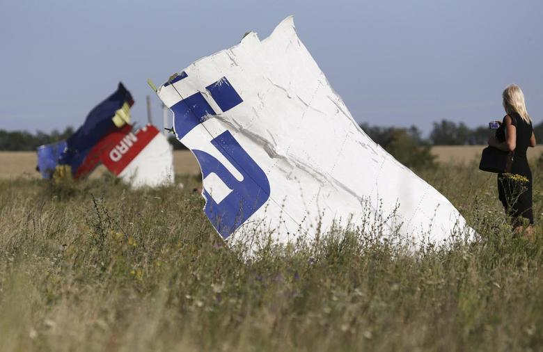 A woman takes a photograph of wreckage at the crash site of Malaysia Airlines Flight MH17 near the village of Hrabove (Grabovo), Donetsk region July 26, 2014.  REUTERS/Sergei Karpukhin