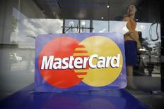 An employee stands behind a MasterCard logo during the launch of the international credit card issuer's first ATM transaction in Myanmar, in Yangon November 15, 2012. REUTERS/Soe Zeya Tun
