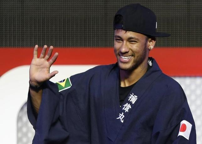 Brazilian soccer player and Barcelona forward Neymar waves as he wears a ''Yukata'', a casual summer Kimono, after receiving it as a souvenir from the organizer during a fan event in Tokyo July 31, 2014. REUTERS/Yuya Shino