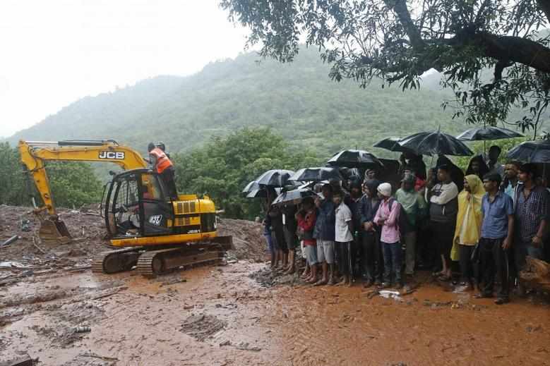 National Disaster Response Force (NDRF) personnel clear the debris as onlookers watch at the site of a landslide at Malin village in the western Indian state of Maharashtra July 31, 2014.  REUTERS/Shailesh Andrade