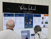 Festivalgoers look at a noticeboard listing details of the day's events at the Verbier Festival, July 27, 2014. Picture taken July 27, 2014.   REUTERS/Michael Roddy