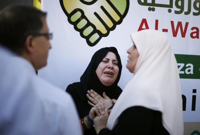 Relatives of Palestinians, whom medics said were killed in an Israeli air strike on their van, grieve at a hospital Gaza City July 31, 2014.  REUTERS/Suhaib Salem