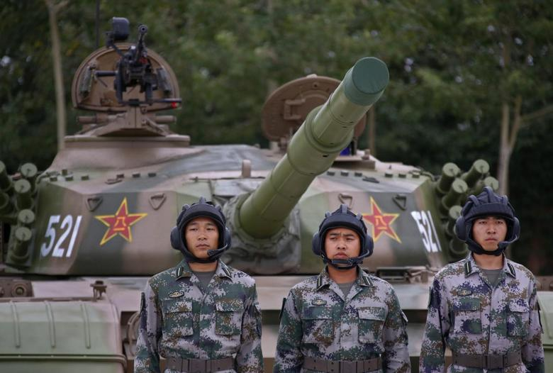 Soldiers of People's Liberation Army (PLA) stand in front of a tank in a drill during a organized media tour at a PLA engineering school in Beijing, July 22, 2014. REUTERS/Petar Kujundzic