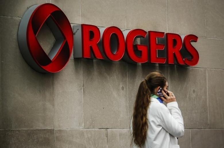 A woman speaks on her cell phone in front of a Rogers Communications Inc sign before the company's annual general meeting for shareholders in Toronto April 22, 2014.   REUTERS/Mark Blinch