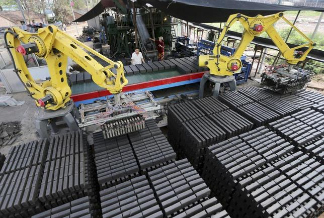Workers look at machines moving newly made raw bricks at a factory in Huaibei, Anhui province July 31, 2014.REUTERS/China Daily