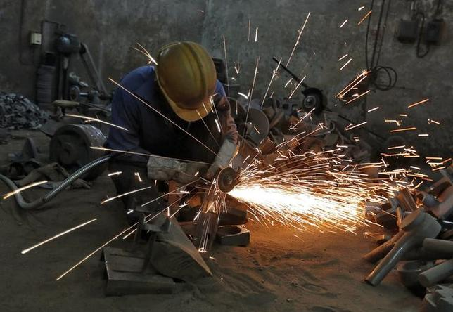 A worker grinds a metal shaft metal used in water pumps at a manufacturing unit on the outskirts of Ahmedabad June 2, 2014. REUTERS/Amit Dave/Files