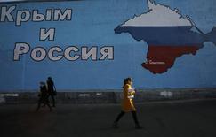 Люди проходят мимо нарисованной на стене карты Крыма в цветах российского флага в Москве 25 марта 2014 года. Крымские футбольные клубы начнут выступление во втором дивизионе чемпионата России по футболу с сезона 2014/2015, сообщил Российский футбольный союз (РФС). REUTERS/Artur Bainozarov