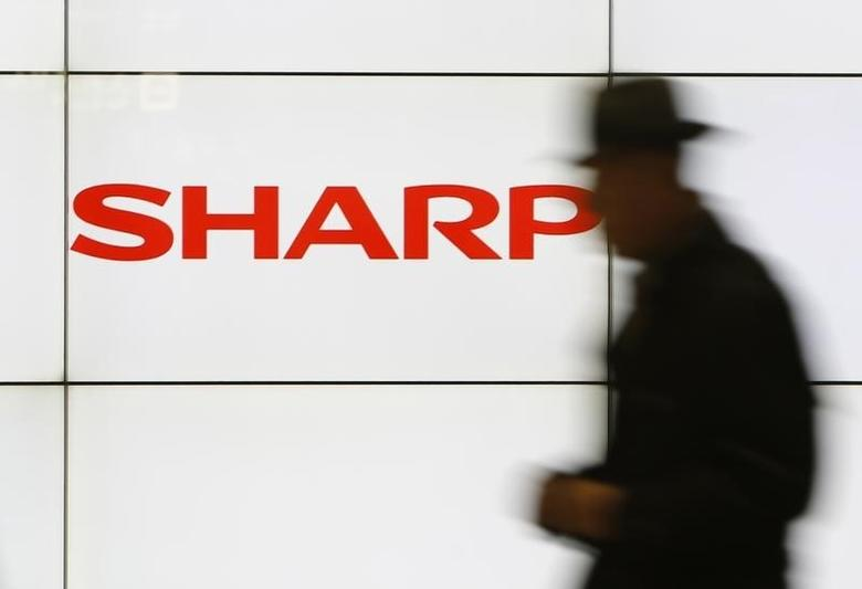 A pedestrian walks past a logo of Sharp Corp at a train station in Tokyo February 3, 2014. REUTERS/Yuya Shino