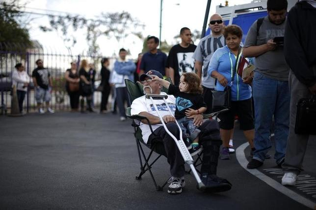 Juan Ortiz, 67, (L) and his eighteen-month-old grandson Joshua Lopez wait in line at a health insurance enrolment event in Commerce, California March 31, 2014. REUTERS/Lucy Nicholson