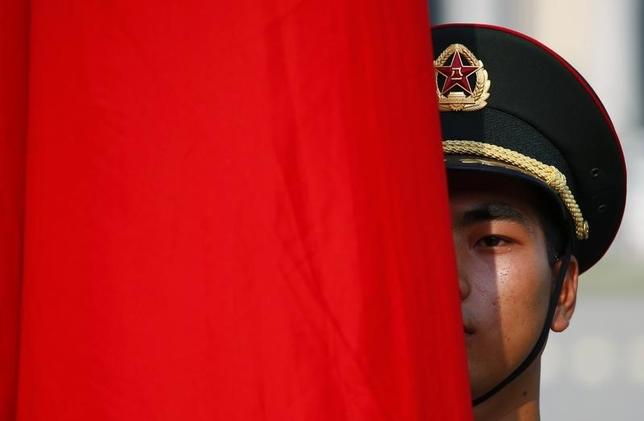 An honour guard member is seen behind a red flag during a welcoming ceremony for Kuwait's Prime Minister Sheikh Jaber al-Mubarak al-Sabah at the Great Hall of the People in Beijing, June 3, 2014. REUTERS/Petar Kujunzic