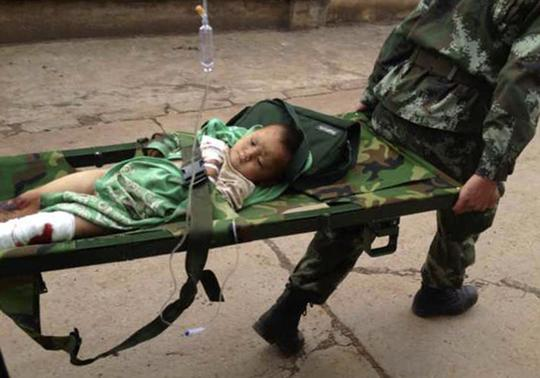 An injured child is carried by paramilitary policemen on a stretcher after an earthquake hit Longtoushan township of Ludian county, Yunnan province August 3, 2014. REUTERS-Stringer
