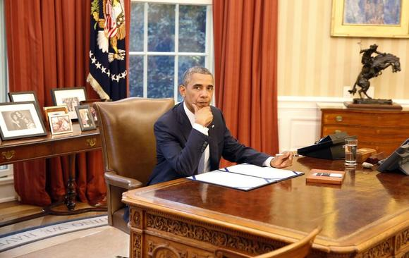 U.S. President Barack Obama reacts before he signs into law S. 517, Unlocking Consumer Choice and Wireless Competition Act, in the Oval Office at the White House in Washington, August 1, 2014.   REUTERS/Larry Downing