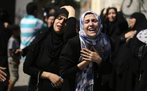 Relatives of nine Palestinians from the Abu Nejim family, whom medics said were killed by an Israeli air strike, mourn during their funeral in Jabaliya refugee camp in the northern Gaza Strip August 4, 2014. REUTERS/Mohammed Salem