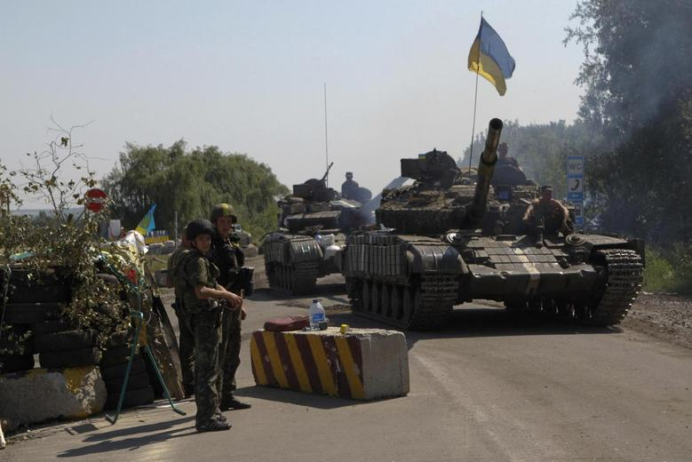Ukrainian army tanks move past a checkpoint as they patrol the area near eastern Ukrainian town of Debaltseve August 3, 2014.  REUTERS/Valentyn Ogirenko