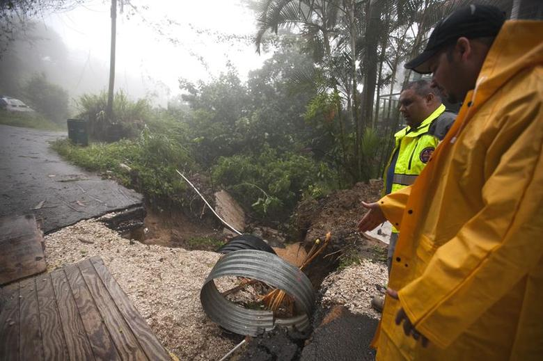 Villalba Mayor Luis Hernandez Ortiz (front, wearing cap) and Pedro Bonilla, director of the Emergency Management Agency, stop to check damages affecting improvements to the aqueduct infrastructure in the sector after heavy rain, in Aceituna town August 2, 2014. REUTERS/Ana Martinez