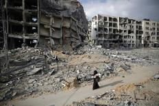 A Palestinian woman walks past buildings destroyed by what police said were Israeli air strikes and shelling in the town of Beit Lahiya in the northern Gaza Strip August 3, 2014. REUTERS/Finbarr O'Reilly
