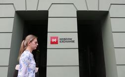 Женщина проходит мимо здания Московской биржи 1 августа 2014 года. Российские фондовые индексы развернулись в ходе торгов понедельника в отрицательную зону во главе с акциями Газпрома, упавшими до минимальной цены за три месяца. REUTERS/Maxim Shemetov