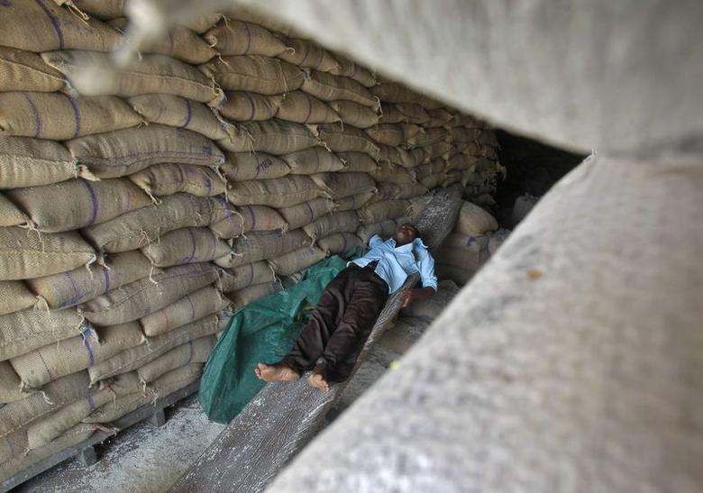 A worker rests inside a rice mill on the outskirts of Agartala, Tripura August 1, 2014. REUTERS/Jayanta Dey